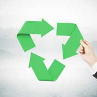 Hand holding recycling symbol on abstract background. 3D Rendering